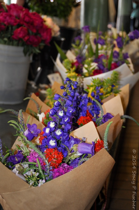 Bunches of brightly colored flowers bundled in paper cones waiting to be sold.