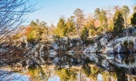Black Pond reflects bedrock bluffs and evergreen trees.