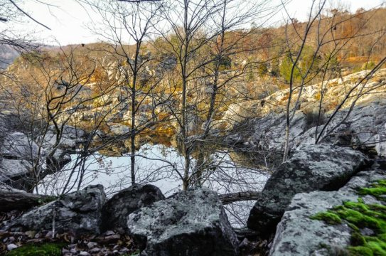 Looking down at the western rocky border of Black Pond in the distance with a boulder outcropping and leafless trees in the foreground.