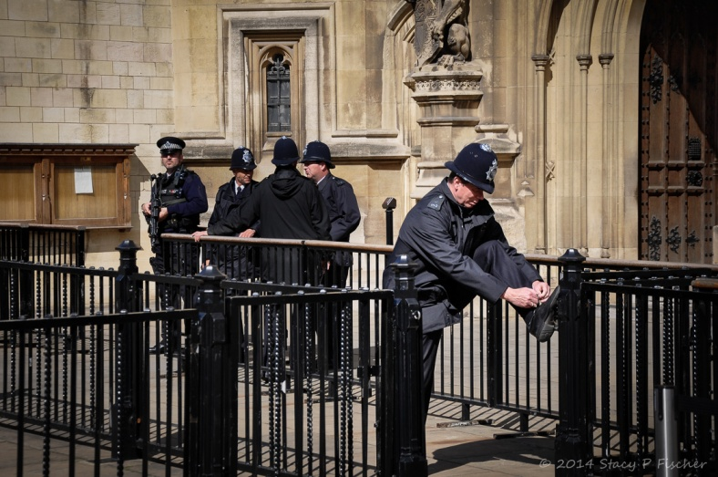 A London Bobby outside the House of Lords props his foot on a railing to tie his shoe.