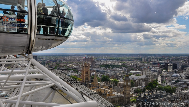 From a capsule atop the London Eye, a view of people in another capsule looking out at the London scene far below.