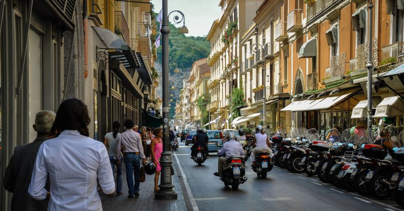 A busy street in Sorrento, filled with pedestrians and lots of motorcyles either being ridden or parked.