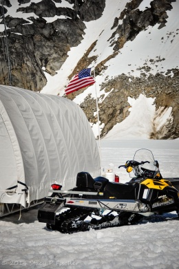 Waving in the breeze, an American flag atop a pole is the backdrop to a musher's tent and yellow snowmobile.