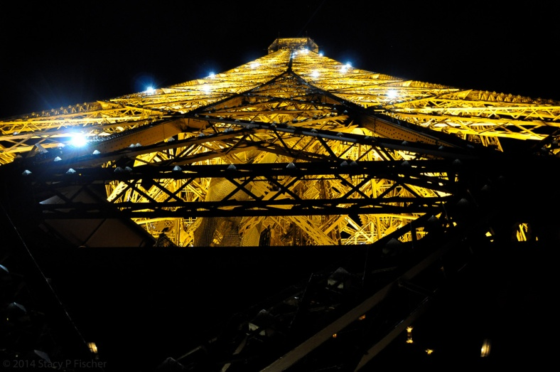 A close-up shot of the top of the Tower from the 2nd floor, with lights twinkling on the golden latticework.