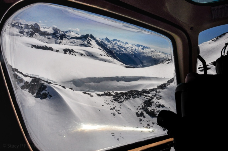 From inside the cockpit of a helicopter, stunnings views of snow-capped mountains, near and far.