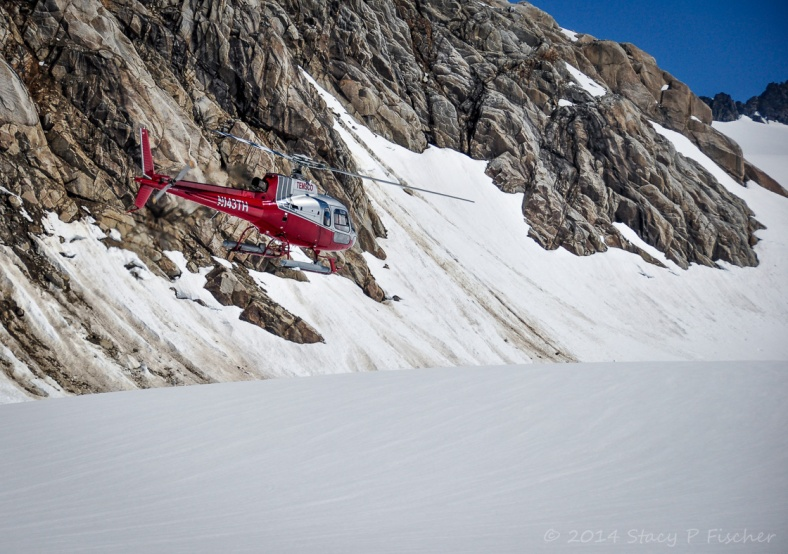 Red helicopter against a backdrop of snow, sheer rock, and blue skies.