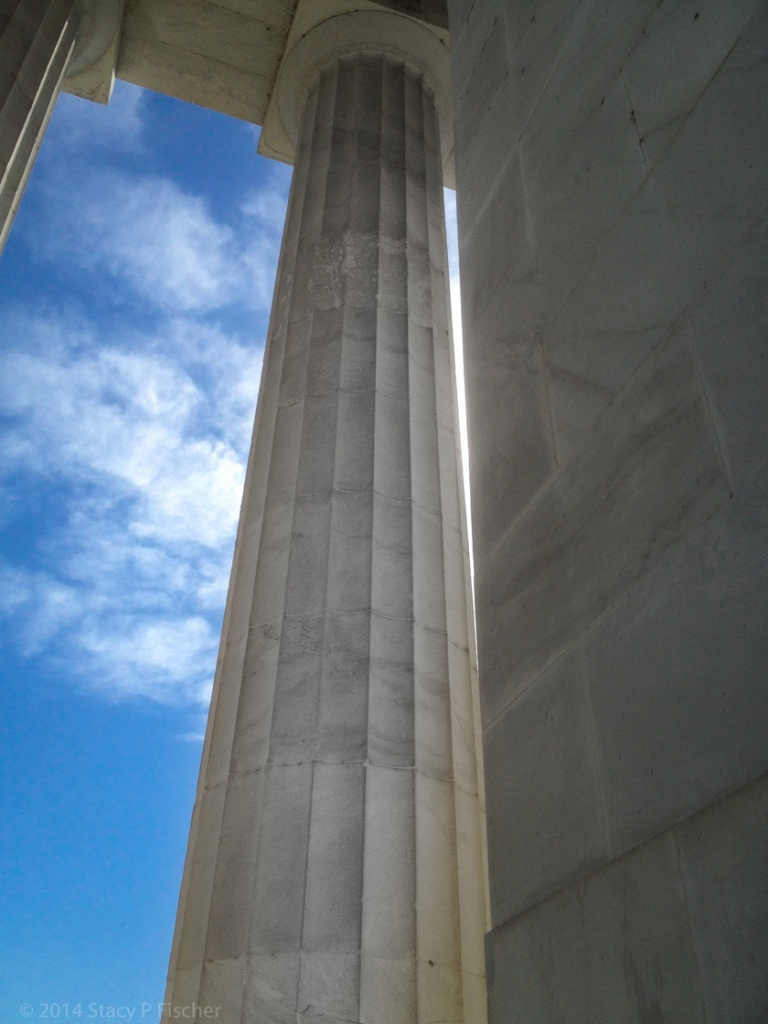 Looking up the height of the column to the top, framed on the left against a deep blue sky and white clouds.