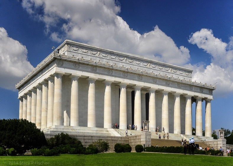 The east and south facades of the Lincoln Memorial, framed against a deep-blue sky dotted with white clouds.
