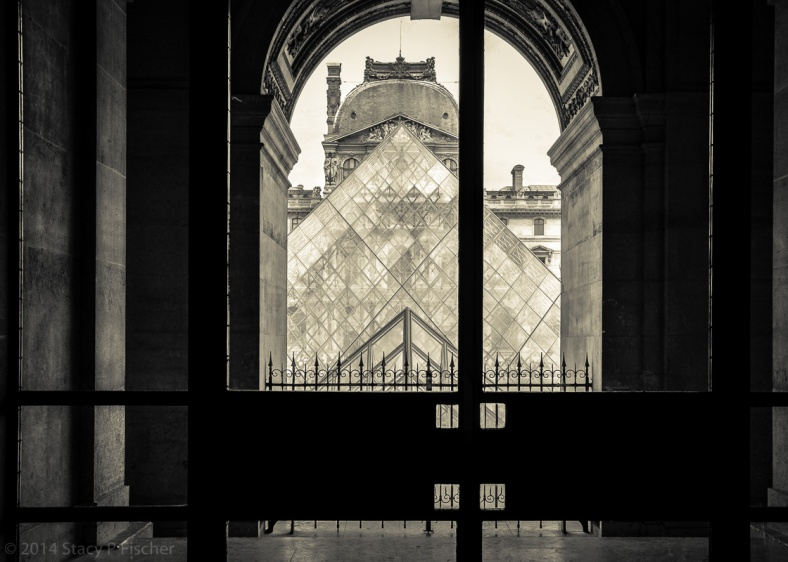 The top of the Pyramid is framed through an archway, with a portion of the Richelieu Pavillion visible through its glass.