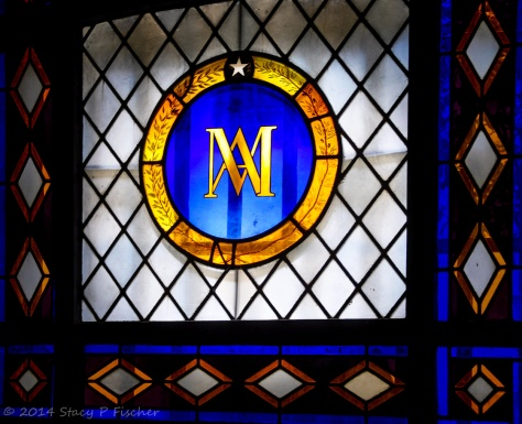 Marie Antoinette's gold initials in a deep blue circle, ringed by an outer gold circle containing olive branches, form a crest on a colorful window.