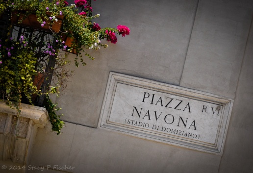 Piazza Novona Street sign in carved stone on the corner of a building, with a flowered balcony to the left.