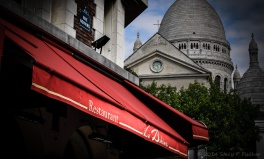 Red canopy of La Bohème Restaurant with a view of Sacré Cœur in the background.