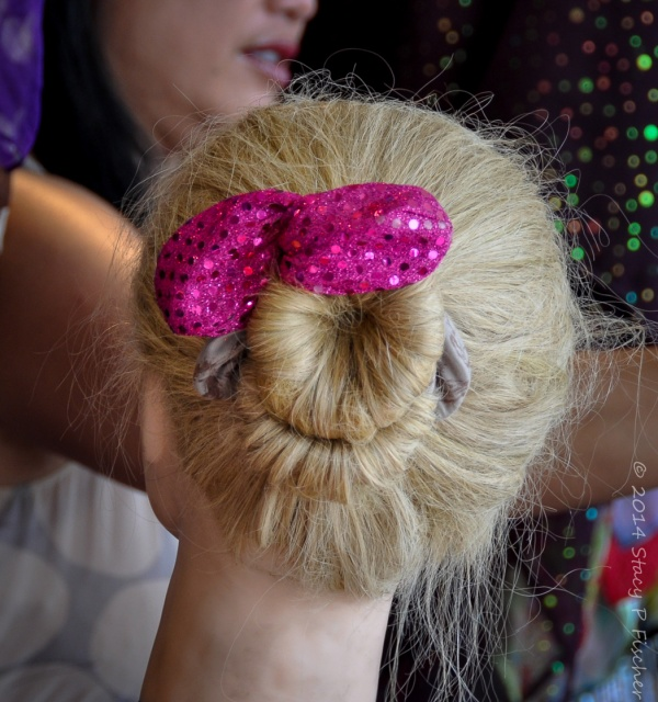 Back of blonde wig on a form fashioned into a ballerina bun with a pink sequined bow.