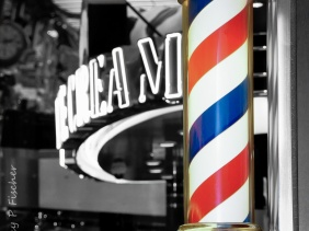Red, white, and blue striped barber pole against black and white interior background