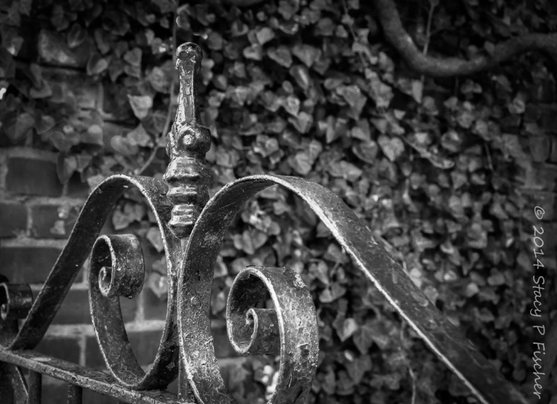 Close-up view of top finial and scrollwork of an iron gate against a backdrop of brick and ivy.