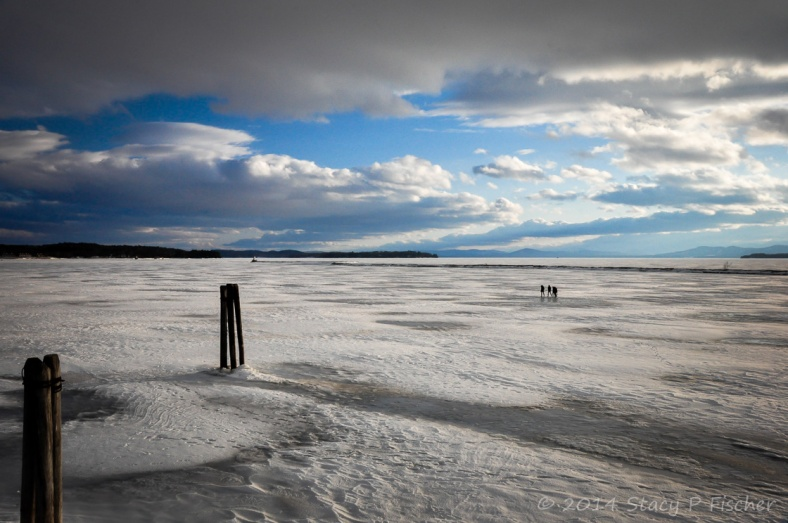 People walking on the frozen surface of Lake Champlain all the way out to the jetty and the lighthouse.