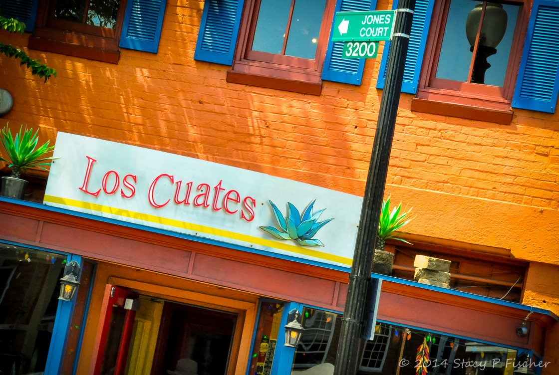 Orange brick, bright blue shutters, red and orange woodworking of Los Cuates Mexican Restaurant.