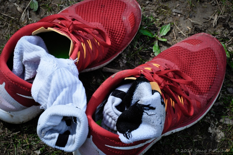 A pair of muddy red tennis shoes stuffed with white socks, sitting on wet ground with hints of green grass and weeds.