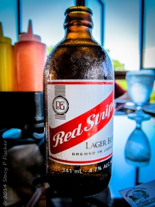 A bottle of Red Stripe covered in condensation, sitting on a tabletop.