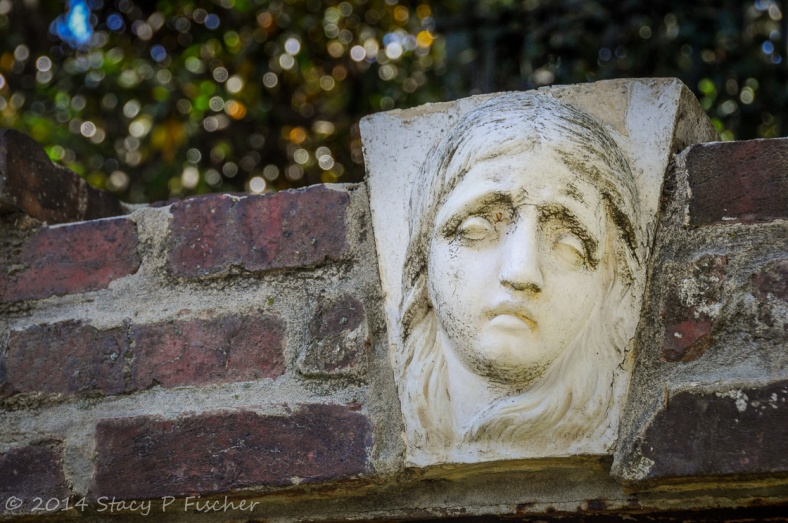 White stone relief of a woman's face and hair in the middle of a brick arch, green-leaved trees softly focused in the background.