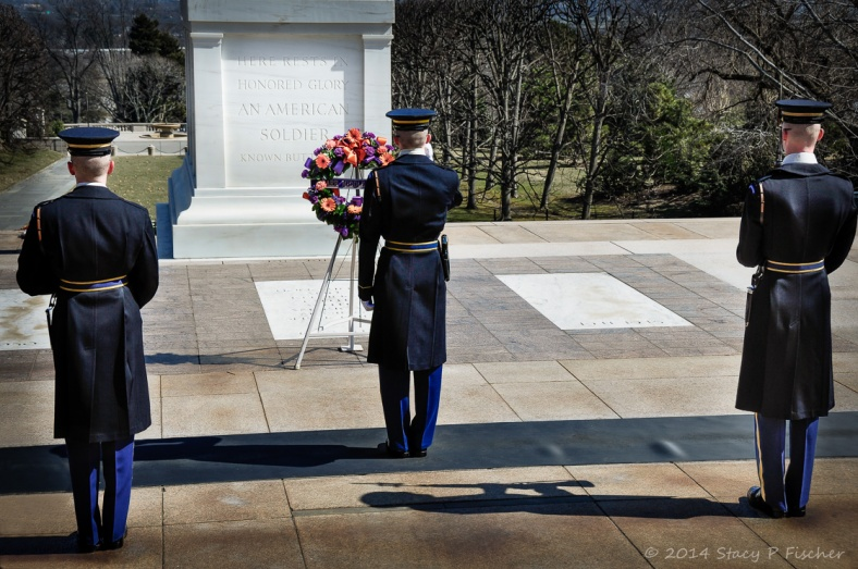 Three Honor Guards face and salute the tombs of the unknown soldiers.