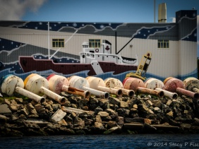 A row of ten weathered buoys on their sides in front of a mural of a tugboat on a waterfront building.