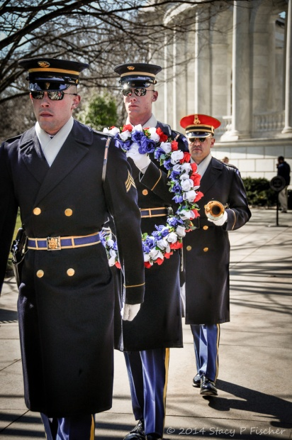 Three Honor Guards, the middle carrying a wreath, the last a bugle, walks single file towards the Tomb.