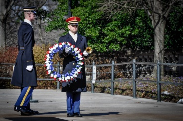 Bugler stands at attention, holding the wreath, while Honor guard clicks his heels.