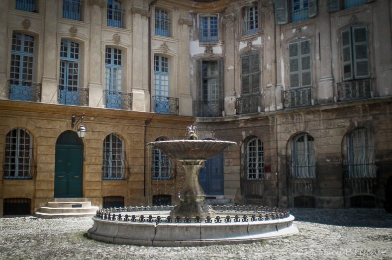 Three-story building with over a dozen blue french doors overlooking a courtyard with a fountain