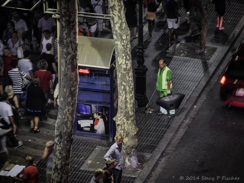 A lone trashman goes unnoticed by nighttime revelers on Barcelona's Las Ramblas.
