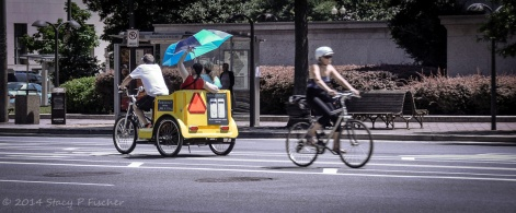 Two passengers in a pedicab heading one direction; another lone cyclicst heading past in the opposite direction.