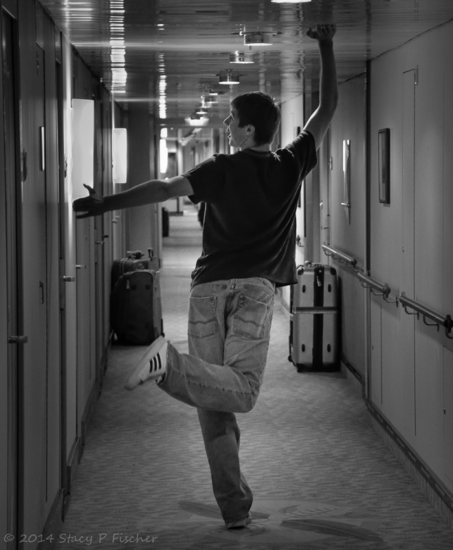 Demonstrating the narrowness of a cruise ship hallway, young man strikes funny pose, touching the ceiling with one hand and the left wall with another.
