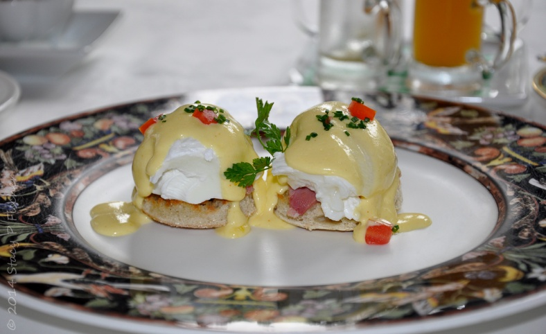 Two petite eggs benedict served on a dark floral rimmed white plate.
