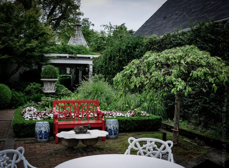 The garden terrace, with red bench, white tables, lush greenery, and goldfish pond