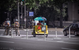 Waiting for the street light on bicycles, in a pedicab, in a car, and on foot.