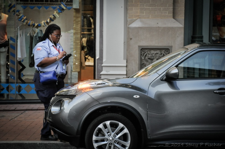 Traffic cop writes a parking ticket for a shiny new car.