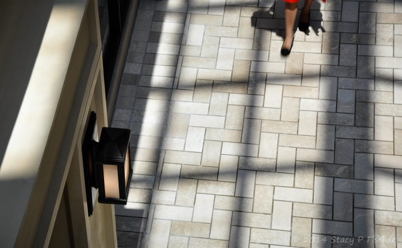 Light through skylights creates shadow grid on white herringbone-patterned flooring