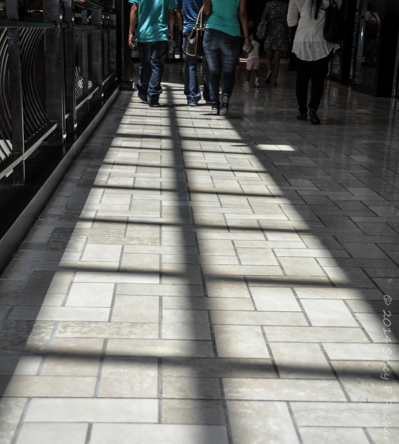 Square shadows fall in a vertical line on the floor of a mall with shoppers at the far end.