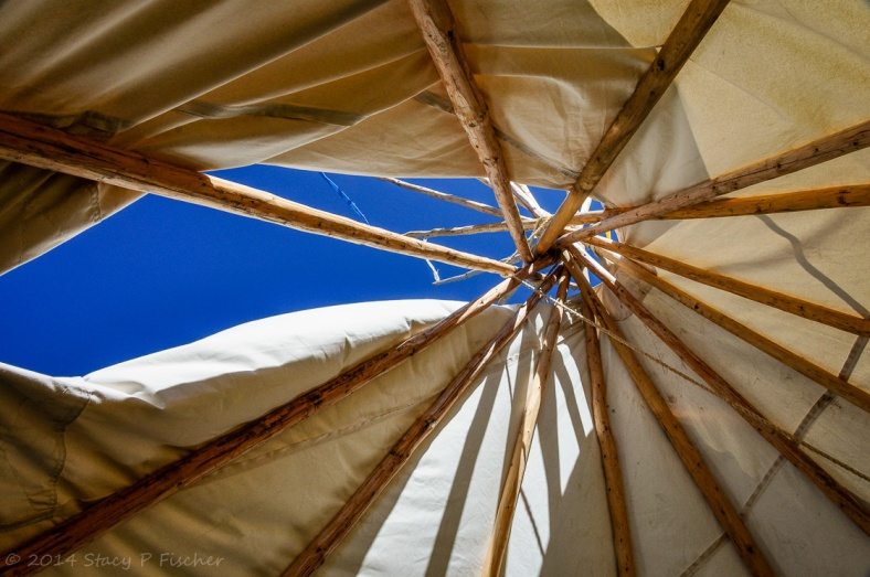 A view inside a teepee looking up to the bright blue sky through the wooden supports.