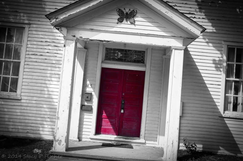 Empty and neglected white wooden building with peeling paint and red double door.