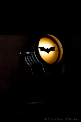 Bathed in shadows the bat-signal glows yellow around the symbol of the bat.
