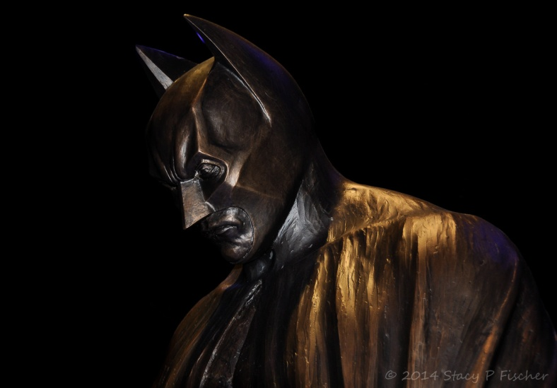 Partial profile view of the head of the Batman statue, bathed in shadows.