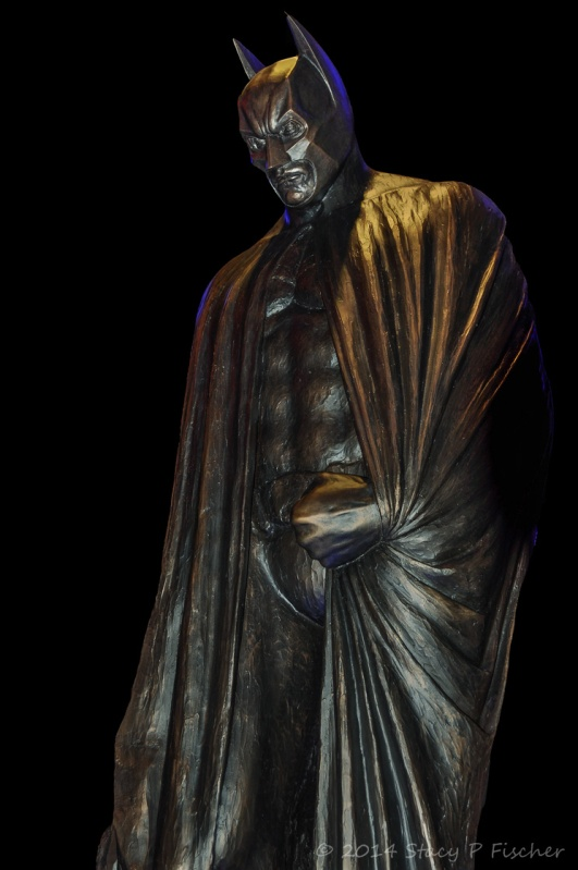 Larger than life statue of Batman bathed in blue lights.