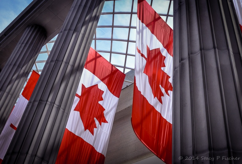 Canadian flags suspended horizontally, framed by marble pillars and overhead glass grid showing a blue sky.