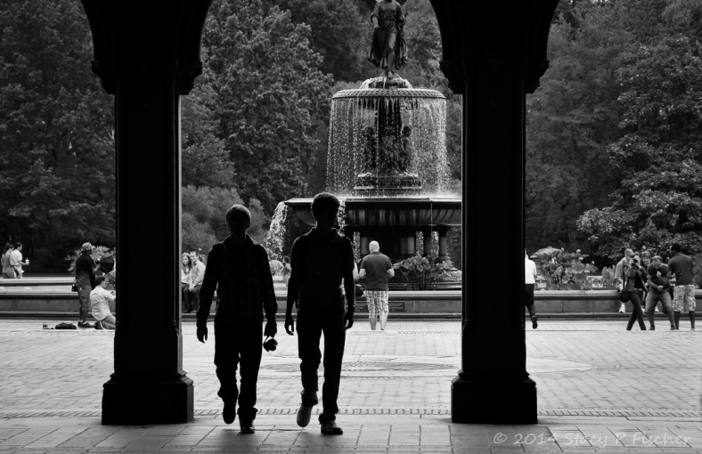 Two young boys silhouetted between two pillars and against a backdrop of a Central Park fountain.