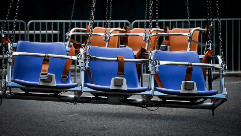 One row of 3 empty blue seats in front of one row of 3 empty orange seats on a carnival ride.