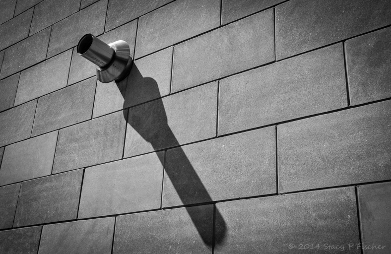 Metal pipe protruding from a brick wall casts a long shadow.