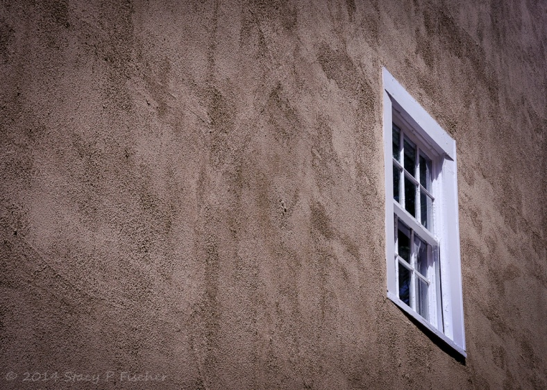 Second-story white window contrasted against a textured brown exterior wall of a house.