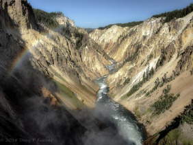 Yellowstone River sporting a rainbow in the foreground winds through canyon after tumbling over Lower Falls.