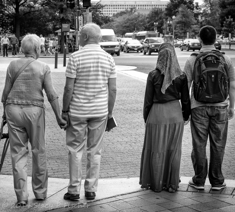 Two couples, one elderly and one young adults, holding hands as they wait to cross the street.